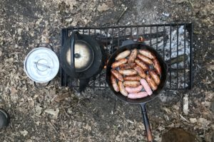 sausages cooking over a fire in the woods